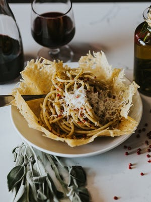 A buttery pasta pepper dish served in a Parmesan cheese bowl.