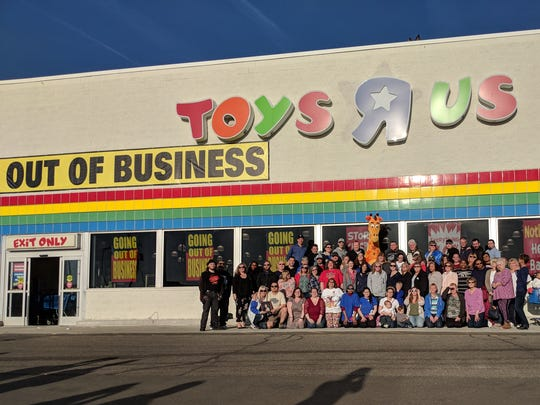 Toys R Us mascot Geoffrey the Giraffe posed with employees who worked at the Roseville location of the closing toy store during a final gathering.
