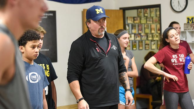 Still a Michigan Wolverine at heart is former football center Jake Sweeney (center). Group exercise sessions at his Canton facility are all about trust, accountability and being part of a team.
