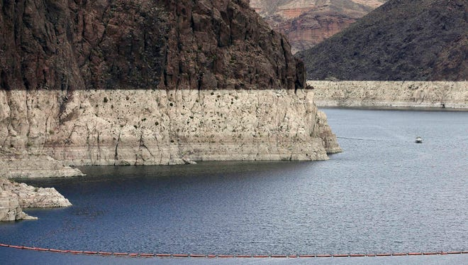 """In this April 16, 2013 photo, a """"bathtub ring"""" marks the high water mark as a recreational boat approaches Hoover Dam along Black Canyon on Lake Mead, the largest Colorado River reservoir, near Boulder City, Nev. Scientists say global warming may already be shrinking the Colorado River and could reduce its flow by more than a third by the end of the century."""