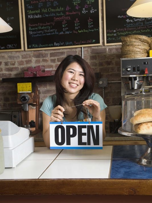 Woman with open sign in shop