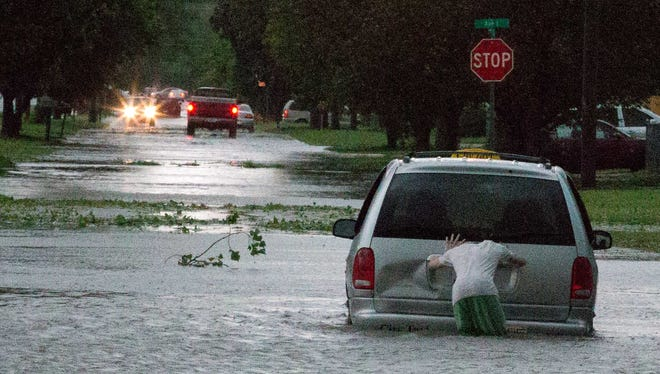 A man tries to push a cab from standing water near North 17th Street and Ave J in Council Bluffs, Iowa,  Tuesday, June 3, 2014. Severe weather crossed into Nebraska and Iowa on Tuesday as potentially dangerous storms targeted a swath of the Midwest, including states where voters were casting ballots in primary elections.