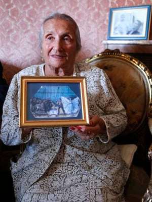 Rosa Bouglione, 103, shows an art piece depicting her and her husband during their circus days, in her Paris apartment. Madame Rosa was born in Belgium to a performing family in time for Christmas in 1910, and though the indefatigable centenarian lived through two world wars, and lost the circus briefly during the Nazi-occupation of Paris, she's never let the trials of the 20th century spoil her zest for life.