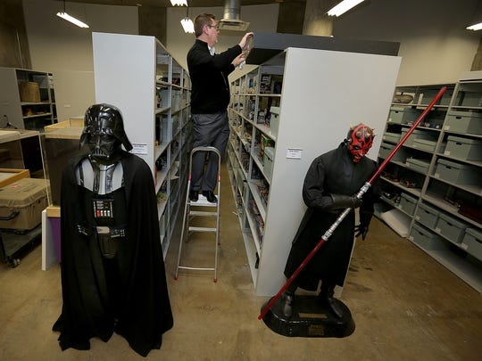 "Christian Carron, director of collections at the Children's Museum of Indianapolis, is flanked by two notable bad guys from the ""Star Wars"" saga. At left is an ""Ultimate Edition Darth Vader Costume,"" which debuted in 2005. Today, online retailers sell the costume for $700. At right is a Frito-Lay promotional statue of Darth Maul. Seen in supermarkets when ""Star Wars"" film ""The Phantom Menace"" was released in 1999, this Darth Maul item is now valued at more than $1,000."