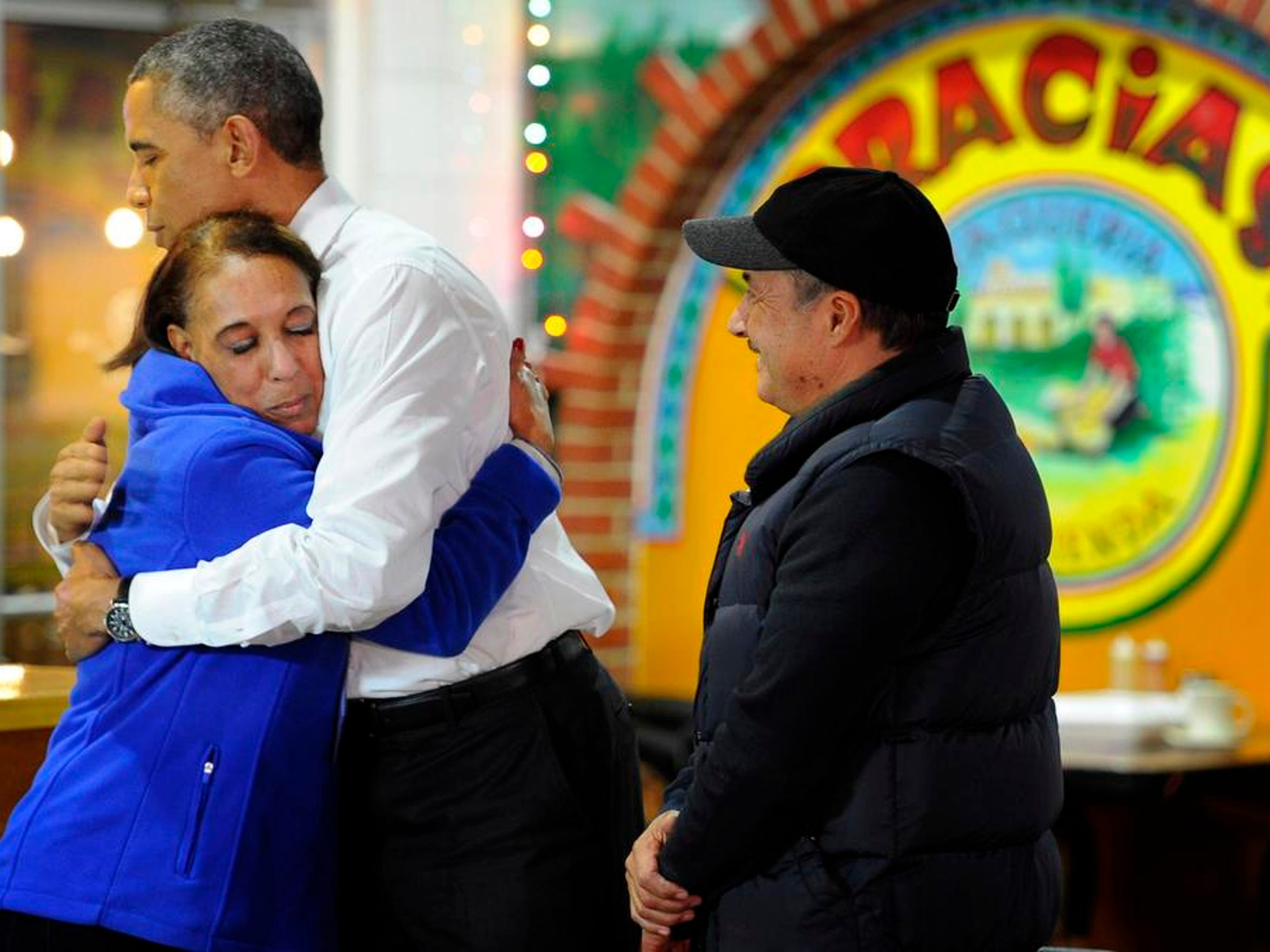 President Barack Obama hugs Lilia Yepez as he visits with Carlos Yepez during a visit to La Hacienda Taquiera on Nolensville Rd. Tuesday Dec. 9, 2014, in Nashville, Tenn.