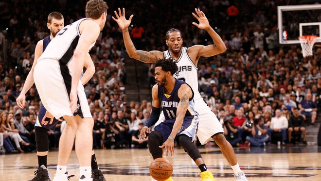 Memphis Grizzlies point guard Mike Conley (11) dribbles the ball as San Antonio Spurs small forward Kawhi Leonard (behind) defends during the first half in game five of the first round of the 2017 NBA Playoffs at AT&T Center.