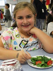 Central 3rd grader Ashley Parker enjoys a true farm-to-table experience with fresh produce from the school garden