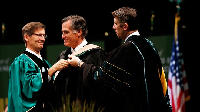 Steven J. Lund, left, chair of the UVU Board of Trustees, and UVU President Matthew Holland, right, present former Massachusetts governor Mitt Romney with an honorary doctorate of business at Utah Valley University's commencement ceremony in Orem, Utah, Thursday, April 30, 2015. Last year, he delivered a religion-focused speech at the nearby Brigham Young University, his alma mater. (Spenser Heaps/The Daily Herald via AP) MANDATORY CREDIT