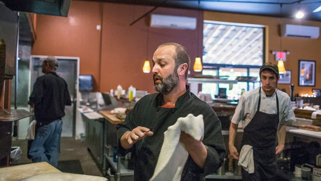 Peter Affatato, center, owner and chef of Nona Mia, makes a pizza while other employees make pasta dishes, salads and more at the West Asheville Italian kitchen and deli on Tuesday evening.