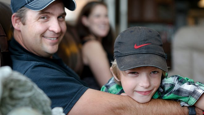Seven-year-old Easton Davison hangs out with his dad, John, and mom, Julie, at their Havre home in September 2013.