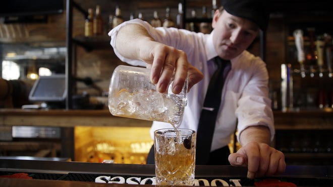 Mark Cunningham makes an old fashioned at Wiseguy Lounge. The bar will host the Cincinnati Bartenders' Guild membership drive on Sunday.