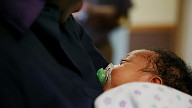 Salome Nengean holds her newborn son Wednesday. Micah was born June 4, measuring 20 inches long and weighing 7 pounds.