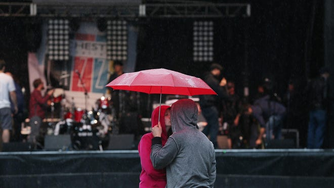 """Alex Wolf gets a kiss from Sam Dzuranin as they wait for Trombone Shorty on the ninth and final day of the Xerox Rochester International Jazz Festival on Saturday. """"Rain doesn't ruin music"""" Dzuranin said."""