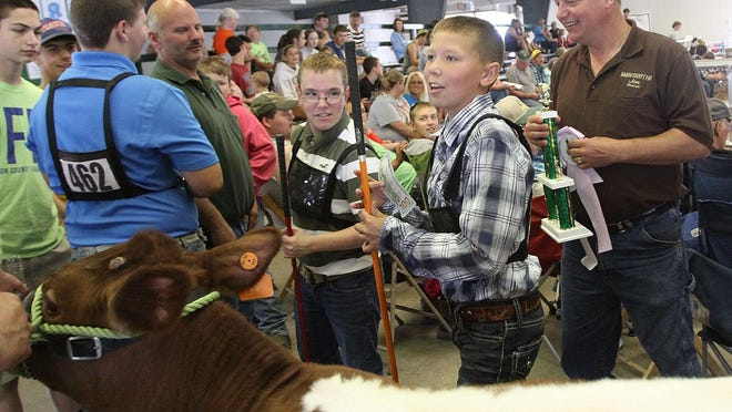Chase Aiken carries the $100 bill he won for having the champion in the beef feeder show at the Marion County Junior Fair on Friday. Brandon Bosley, center, won the reserve champion during the judged competition.