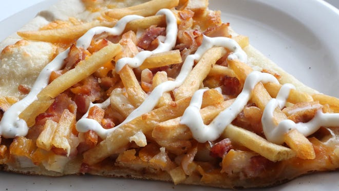 """The """"Out of School"""" slice prepared at Froggy's Pizza and Pasta. The new pizza joint is next door to Froggy's Deli in Somers."""