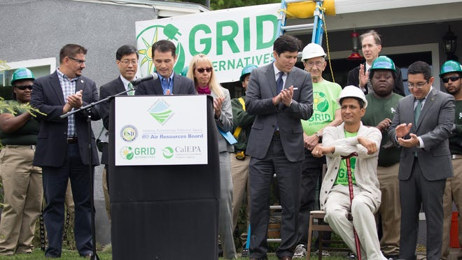 California Senate leader Kevin de Leon (third from right) participates in a ceremony May 18, 2015 during the installation of solar panels on the roof of a South Sacramento home. De Leon is clapping next to Roy Rivera, owner of the house.