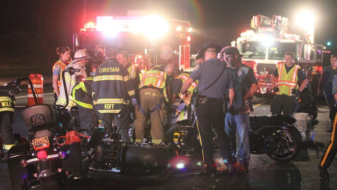 Emergency personnel work at the scene of an accident on Chapman Road involving a car and motorcycles that sent four people to the hospital, reported about 9:45 p.m. Friday.