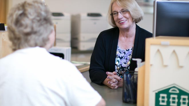 Kathy VanPatten assists a member at Pittsford Federal Credit Union in Mendon on Thursday, July 23, 2015.