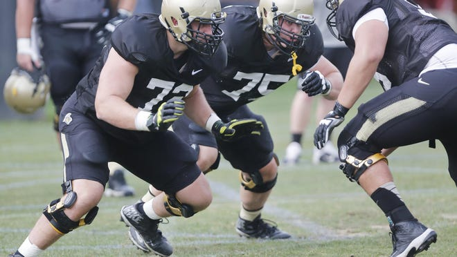 Offensive linemen Jason King, left, and David Hedelin, middle, run through a blocking drill during Purdue football practice Monday, August 10, 2015, on the campus of Purdue University in West Lafayette.