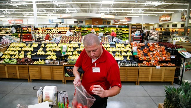 Customer care and education manager Kevin Luensmann inspects an apple before bagging it Wednesday while filling an online shopping order at the Prairie Trail Hy-Vee in Ankeny. Customers can place an order online and pick it up in the store or have it delivered.