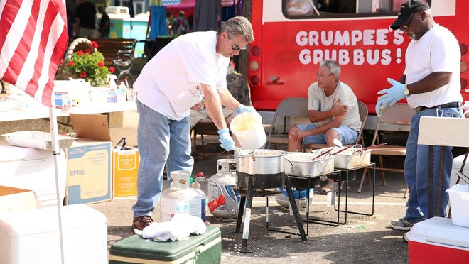 Bob Culver scoops hush-puppy dough into a large fryer for the plates of catfish and hush puppies Saturday afternoon at the McKenzie Fried Food Festival.