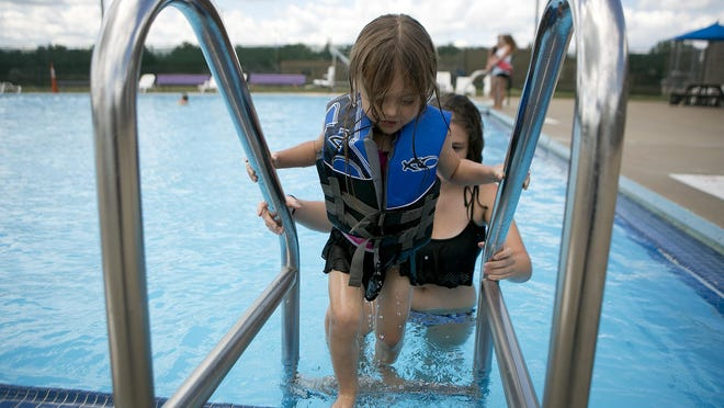 Rachel Gibbs, 17, of Port Edwards, right, helps the girl she is babysitting, Madeline Farragut, 3, left, use the ladder at Mead Pool in Wisconsin Rapids on Aug. 11, 2015.