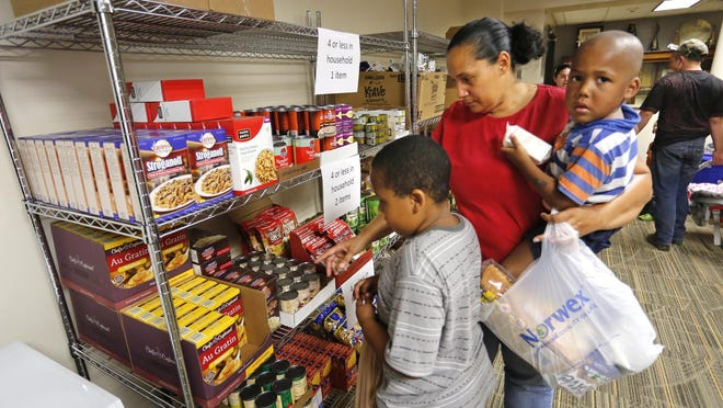With three-year-old son Micheal Meyer in her arms, Joline Meyer points out to her son Jaikeam Jones food items to bag at the food pantry Thursday, September 10, 2015, inside Oakland Elementary School. Oakland Elementary together with Food Finders Food Bank opened the food pantry to help feed students and their families who are struggling with food insecurity. Jaikeam, 7, is a second grade student at Oakland Elementary.