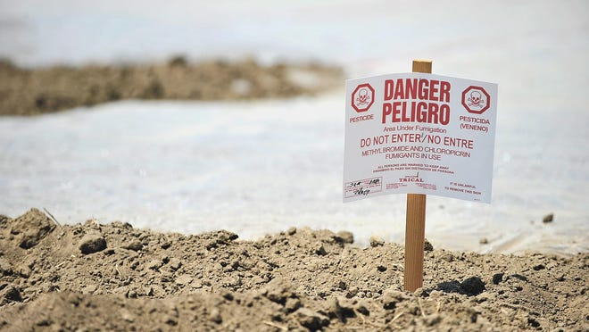 This 2008 file photo shows a pesticide warning sign in a field at Akers Street and Ferguson Avenue in Visalia.