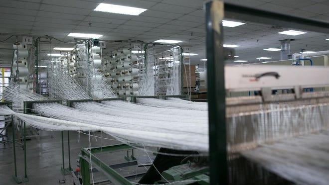 A beamer prepares fiberglass yarn for weaving at Newtex Industries in Victor on Wednesday, November 4, 2015.