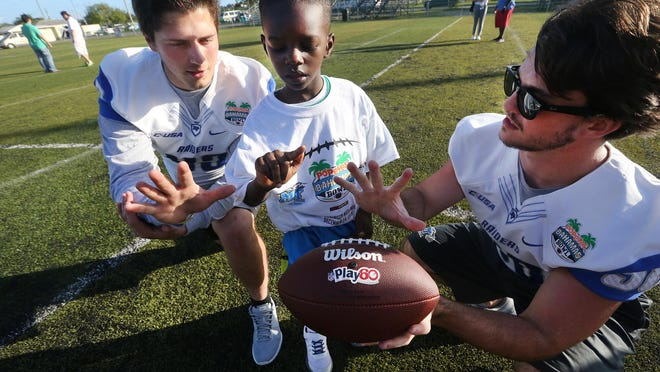 MTSU's football player Trevor Owens (43), left and Jim Cardwell (38) right teach M'ycahi Wilson, 6, how to throw a football during a Youth Football Clinic in connection wth the Popeyes Bahamas Bowl on Dec. 22, 2015.