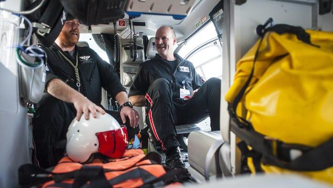 John Rossmiller, left, and Mark Long, right, sit in Benefis' Mercy Flight helicopter Thursday.