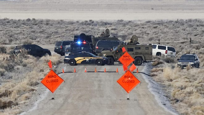 Law enforcement personnel block an access road to the Malheur National Wildlife Refuge on Wednesday near Burns. Authorities were restricting access on Wednesday to the Oregon refuge being occupied by an armed group after one of the occupiers was killed during a traffic stop and eight more, including the group's leader Ammon Bundy, were arrested.