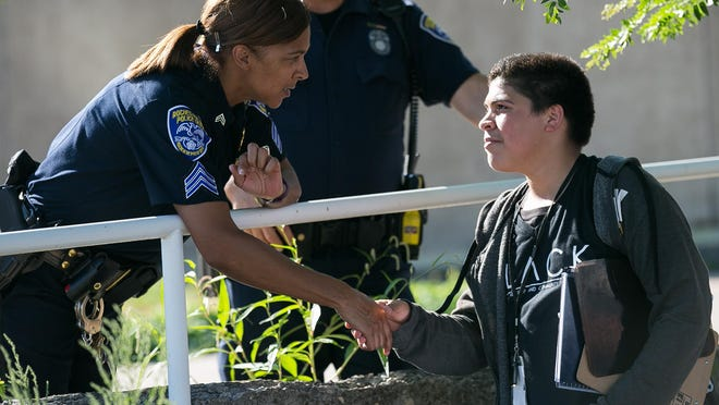 Rochester Police Sergeant Kara Anglin shakes hands with Juan Collado, 16, a co-organizer of a Black Lives Matter protest organized by Latinos Unidos in front of the Rochester Public Safety Building on Thursday, August 4, 2016. Approximately 30 peaceful protesters attended.