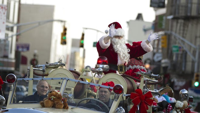 """Santa's firetruck moves along Main Street, followed bu children hoping to catch a stuffed animal. Boonton Christmas Parade on Main Street and """"Shop Small Saturday"""" event, Saturday, Nov. 26, 2016. Boonton, NJ. Special to NJ Press Media/Karen Mancinelli/Daily Record MOR 1126 downtown shopping"""