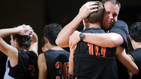 Nocona basketball head coach Bret Botard hugs Marcus Carter (10) after a loss to Canadian in the 3A boys basketball semi-final game Friday, March 3, 2017, at Chaparral Center.