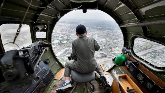 """Nathan Griffin, 11, of Red Bluff looks out the nose of a World War II-era B-17 over Valley skies during a media flight on Thursday. The """"Madras Maiden"""" is one of just 12 B-17s still flying in the world. Flights and tour information is available by calling Scott Maher at 918-340-0243."""