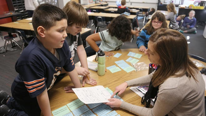 Whittier fourth-grade teacher Kati Nailor works with students Caimyn Marks, Conlan Liventals, Treasure Barbour and Amberlin Hall-Freeman on a reading project on Jan. 27.