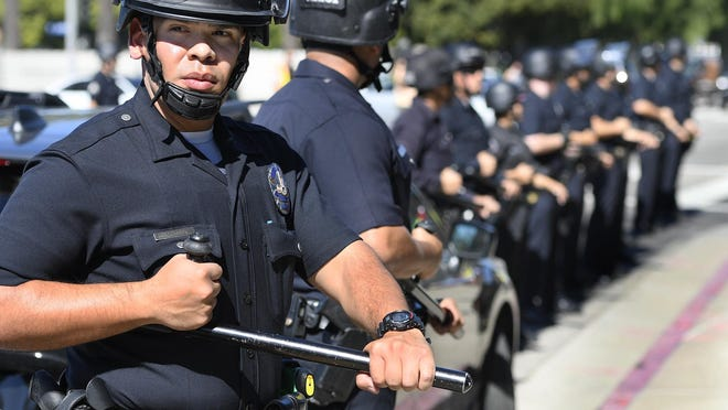 Police officers outfitted in riot gear with batons at the ready keep protesters on the sidewalk on Wilshire Boulevard, outside the Federal Building in Westwood, Calif. DACA supporters took to the street on deadline day for DACA renewals Thursday, Oct. 5, 2017. ( John McCoy/Los Angeles Daily News via AP)