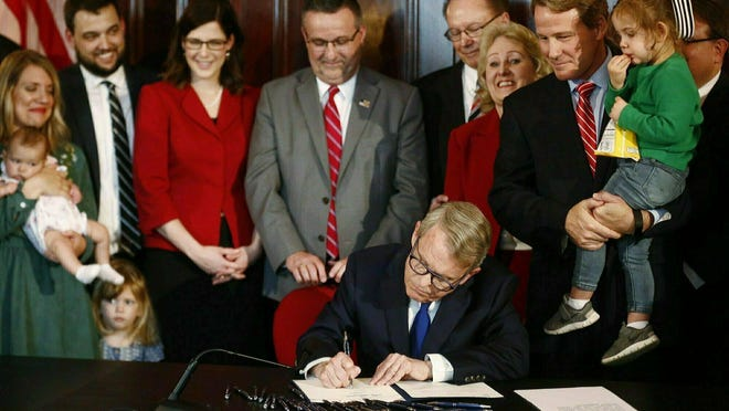 In this April 11, 2019 file photo, Gov. Mike DeWine signs a bill imposing one of the nation's toughest abortion restrictions in Columbus, Ohio. A federal judge has blocked part of an Ohio law that bans the abortion method of dilation and evacuation in most cases.