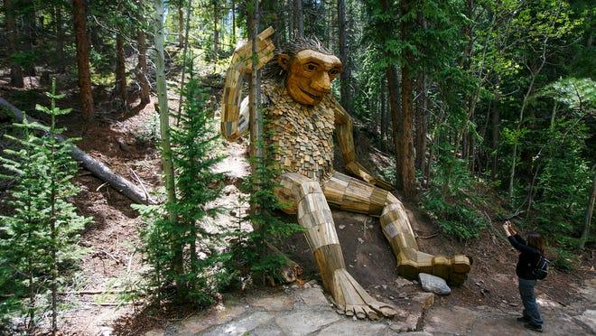 A hiker takes a photo of Isak Heartstone, a large wooden troll built by Danish artist Thomas Dambo, in his new site on the Trollstigen trail in Breckenridge, Colo.