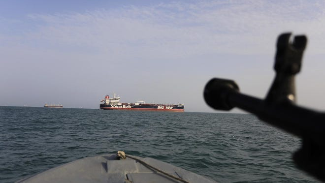 FILE - In this In this July 21, 2019 file photo, a speedboat of Iran's Revolutionary Guard trains a weapon toward the British-flagged oil tanker Stena Impero, which was seized in the Strait of Hormuz on July 19 by the Guard, in the Iranian port of Bandar Abbas. Iranian forces seized a ship in the Persian Gulf suspected of carrying smuggled fuel, state media reported Sunday, Aug. 4, 2019, marking the Revolutionary Guard's third seizure of a vessel in recent weeks and the latest show of strength by the paramilitary force amid a spike in regional tensions. State TV and the semi-official Fars news agency reported that seven crew members were detained when the latest ship was seized late Wednesday. (Morteza Akhoondi/Tasnim News Agency via AP, File)