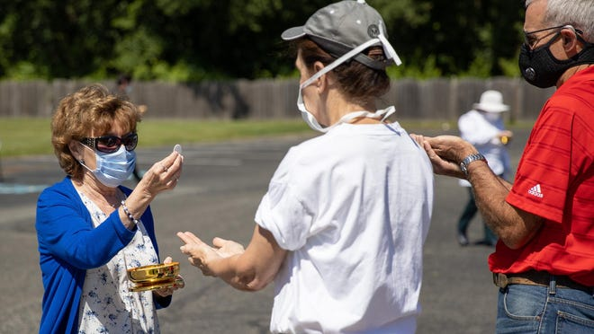 Parishioners receive Holy Communion in the parking lot of St. Mary of the Lakes Church in Medford on Sunday. The parish has taken to having Mass outside amid the coronavirus outbreak.