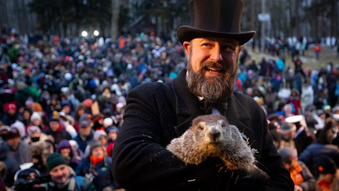 A member of the Punxsutawney Groundhog Club's Inner Circle holds Phil for a picture after he makes his weather prediction on Groundhog Day at Gobbler's Knob in Punxsutawney, Pa., on Feb. 2.  The best way to keep those winter-time blues from getting you down is to stay active outside doing things you wouldn't want to spend time doing during the hot growing season.