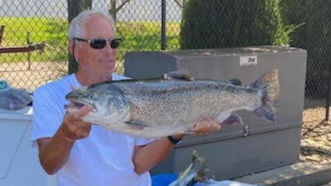 Robert Ferraro shows the 20-pound, 9-ounce brown trout he caught Aug. 8 on Lake Erie. If it is certified, the trout would be a state record for its species.