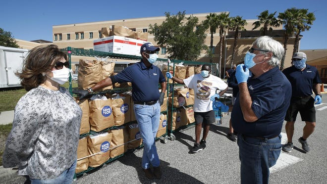 Forough Hosseini with volunteers with Food Brings Hope, ICI, Embry Riddle and Sodexo hand out grocery bags full of food during a food giveaway at Mainland High School in Daytona Beach, Thursday, May 7, 2020.
