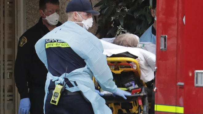 A patient is loaded into an ambulance, Tuesday, March 10, 2020, at the Life Care Center in Kirkland, Wash., near Seattle. The nursing home is at the center of the outbreak of the COVID-19 coronavirus in Washington state.