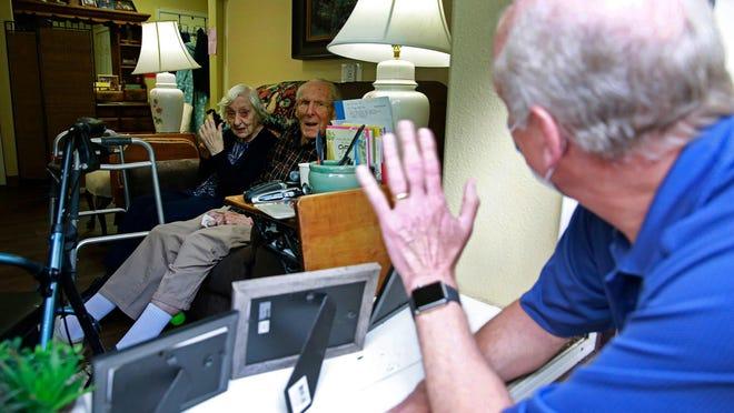 Barbara Kuhn (left) and Blaine Kuhn talk to their son, Steve Kuhn, through a window at Prestige Senior Living Orchard Heights in Salem on June 3.