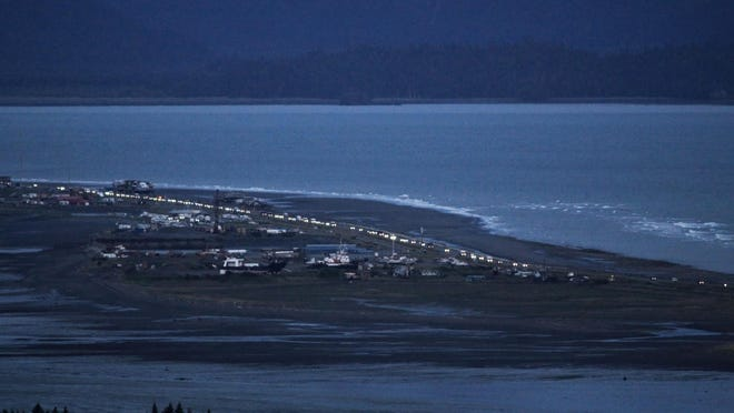 Headlights from a line of cars shine at dusk as people evacuate the Spit in Homer, Alaska, following a powerful earthquake in the Aleutian Islands that prompted a tsunami warning. There were no immediate reports of damage in the sparsely populated area of the state, and the tsunami warning was later canceled.