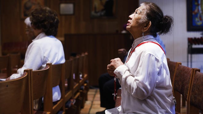 Esther Gianan, of Tampa a retired registered nurse prays for those who are affected by the coronavirus during Mass Friday at St. Lawrence Catholic Church in Tampa.