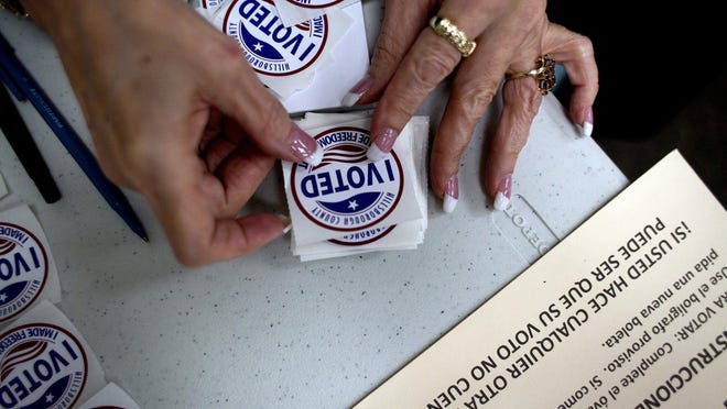 """A poll worker gets """"I Voted"""" stickers ready to hand to voters as they finished up at the ballot booths at Jan Kaminis Platt Regional Library in South Tampa, Fla., on November 6, 2012."""